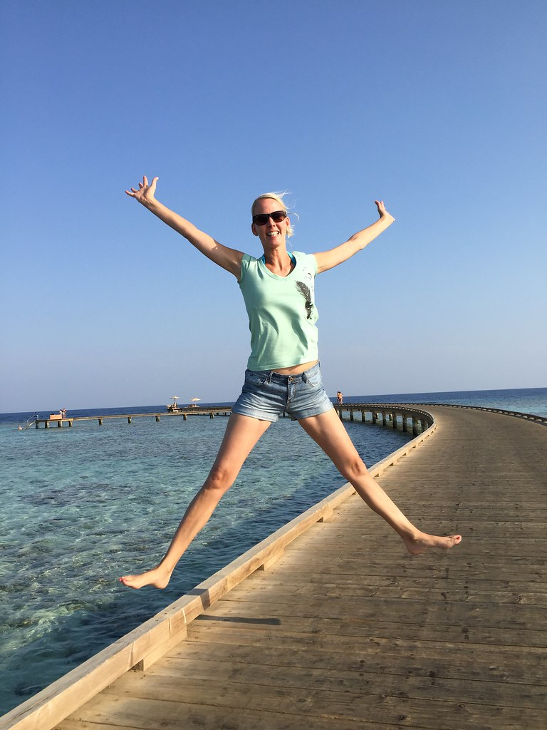 A woman jumping for joy on a dock with ocean behind her.
