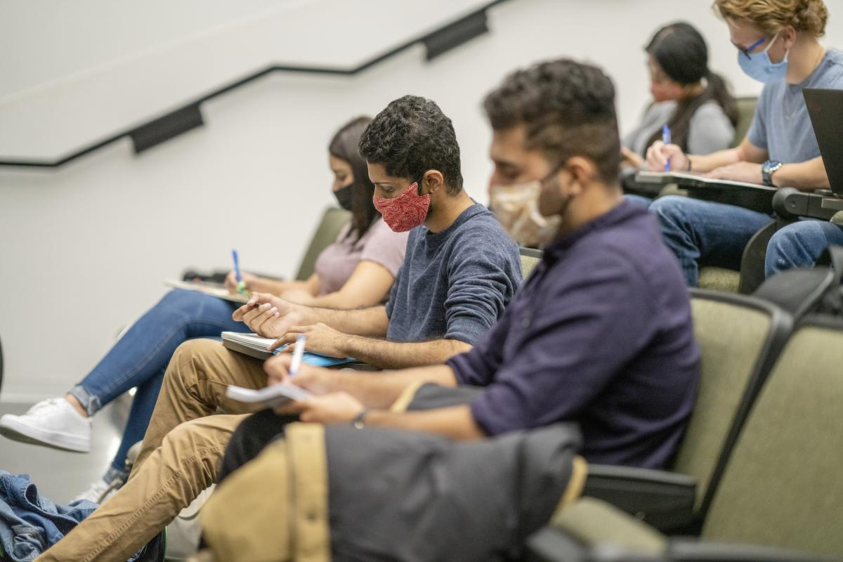 Masked students who are socially distanced in a lecture hall